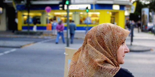 395629 01: A Muslim woman waits to cross a street October 10, 2001 in Berlin's heavily-Muslim Neukoelln...