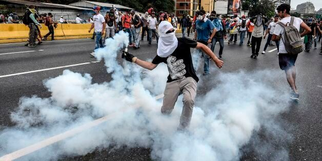 TOPSHOT - Demonstrators clash with the riot police during a protest against Venezuelan President Nicolas...