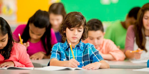 A multi-ethnic group of elementary age children are sitting at their desks are are writing in their