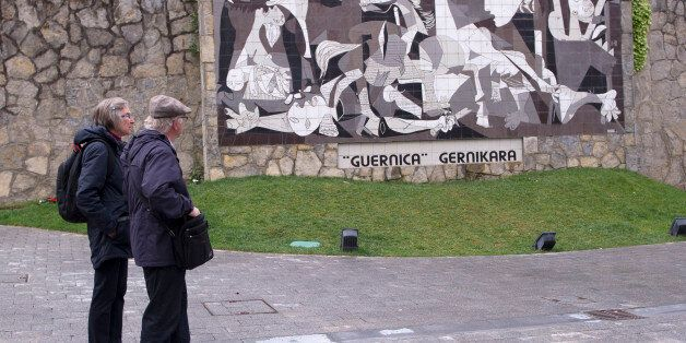 A couple watch a mural depicting Picasso's painting 'Guernica' in the Spanish northern Basque village...