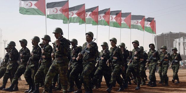 Members of the Sahrawi People's Liberation Army parade with Polisario Front's flags during a ceremony...
