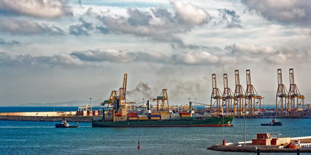 Containership arriving port Valencia with the assistance of two harbour tugs. Spain,