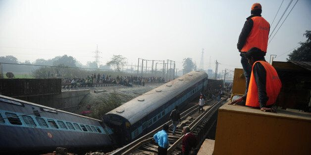 Indian officials and bystanders gather alongside derailed train carriages at Rura, some 30 kms west of...