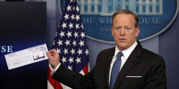 White House Press Secretary Sean Spicer shows a check from U.S. President Donald Trump's salary which...