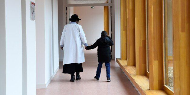 A nursing auxiliary and a child walk on March 21, 2017 in Neuilly-Plaisance, near Paris, in the new day...