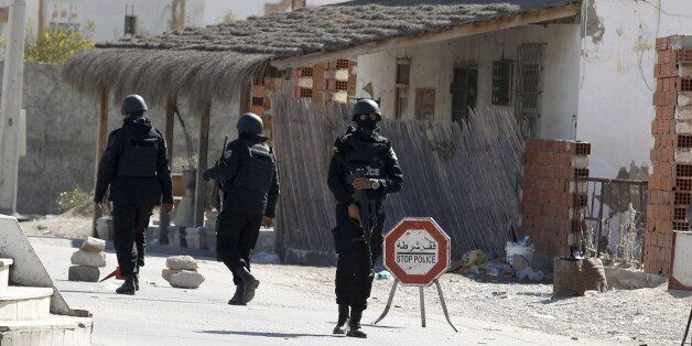 Tunisian police officers stand guard near a police station after Monday's attack by Islamist fighters...