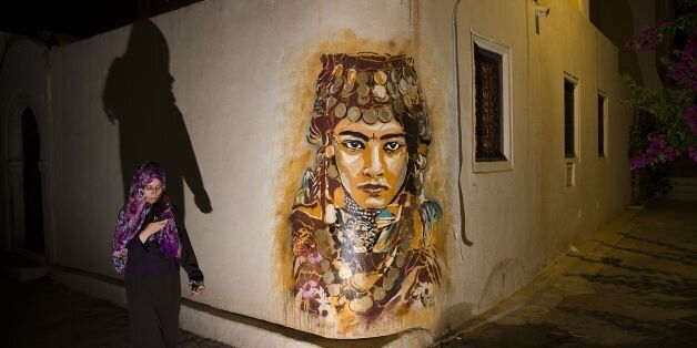 A woman walks past a mural by Spanish artist B-TOY in the village of Erriadh, on the Tunisian island...