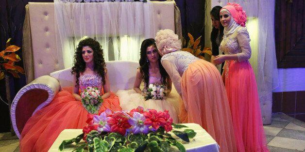 QAMISHLI, SYRIA - NOVEMBER 11: Kurdish brides Halbast Khalili, 21, (L), and Mezgin Murat, 21, (C), are...