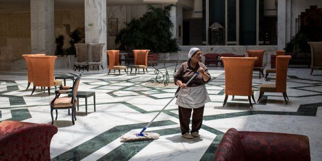 SOUSSE, TUNISIA - JUNE 24: An employee mops the lobby floor at the closed Imperial Marhaba Hotel on June...