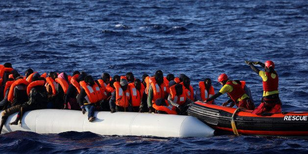 Rescuers help migrants on an overcrowded plastic raft board a RHIB during a search and rescue operation...