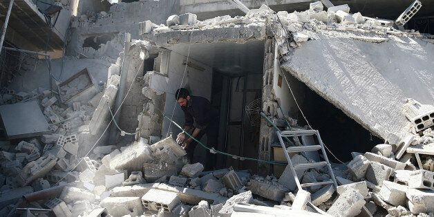 A man removes rubble at a damaged site after airstrikes in the rebel held besieged Douma neighborhood...