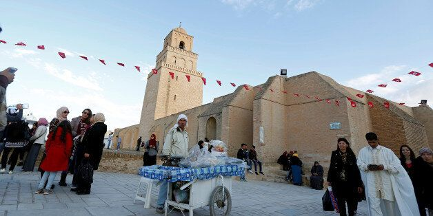 People pass a street vendor selling traditional confectioneries in front of the Uqba ibn Nafi mosque,...