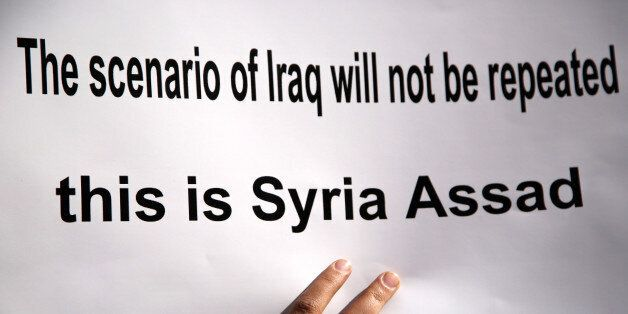 A placard is pictured during a protest against American airstrikes in Syria, in front of the United Nations...
