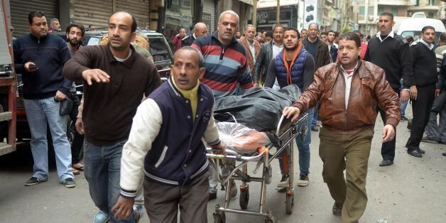Egyptians wheel away a body near a church in Alexandria after a bomb blast struck worshippers gathering...