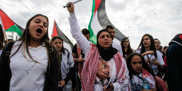 A female demonstrator waves a Palestinian flag during a demonstration marking Land Day on March 30, 2017...