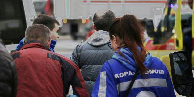 An injured person is helped by emergency services outside Sennaya Ploshchad metro station, following...