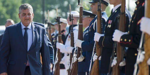 Belgium's Defense Minister Steven Vandeput walks past an honor guard as he arrives to attend a meeting...