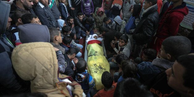 Palestinian relatives of 18-year-old Yousef Abu Azra sit around his body in Al-Awda mosque during his...