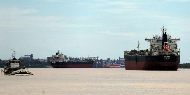 Ships used to carry grains for export are seen next to a dredging boat (L) on the Parana river near Rosario,...
