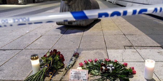 Candles and flowers are placed near the site where a beer truck crashed into the department store Ahlens...