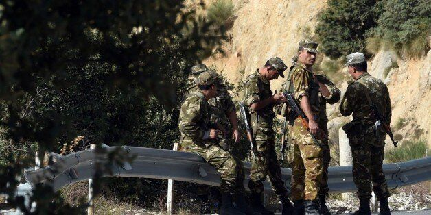 Algerian troops rest as they conduct a search operation on October 10, 2014, near the village of Ait...