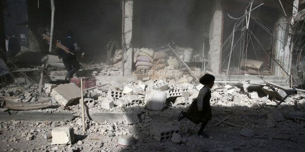A girl runs past a damaged site after an airstrike in the besieged rebel-held town of Douma, eastern...