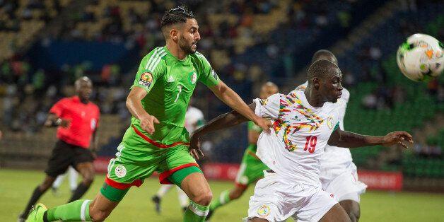 FRANCEVILLE, GABON - JANUARY 23: RIYAD KARIM MAHREZ of Algeria and SALIOU CISS of Senegal during the...