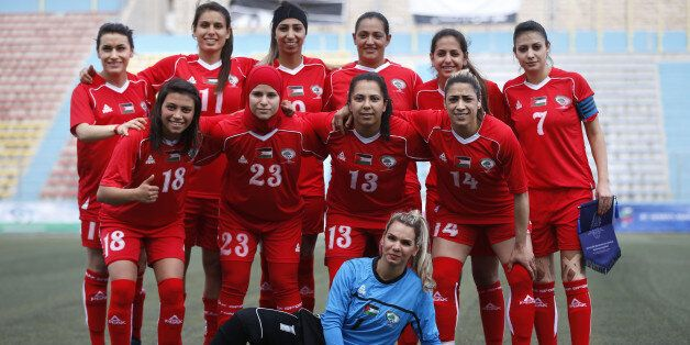 Palestinian female football players (in red) are seen during a qualifying match against Thailand for...