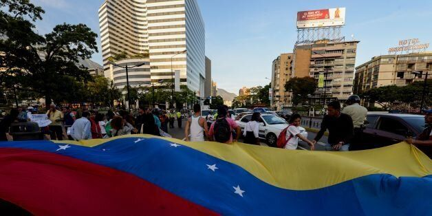 Venezuelan opposition activists, display a national flag during a march against President Nicolas Maduro's...