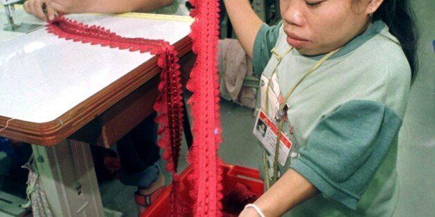 Handicapped Thai worker Consa Chumpra, 24, works on quality control of lace to be used to make womens...