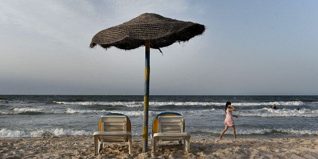 SOUSSE, TUNISIA - JUNE 22: A young girl walks past an unoccupied parasol on the beach of the once popular...