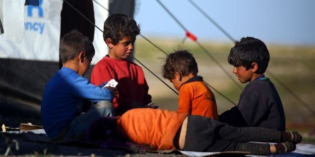 Syrian children play cards at a temporary refugee camp in the village of Ain Issa, housing people who...