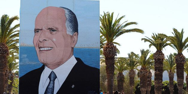 Tunisian wait next to a giant poster of former Tunisian president Habib Bourguiba as they attend an anniversary...