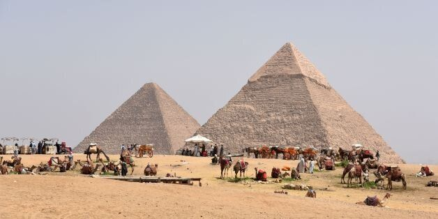 Egyptian camel owners wait for tourists outside the pyramids, on the Giza Plateau, on the southern outskirts...