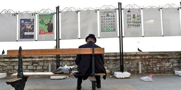 Un homme assis devant des panneaux de campagne électorale à Alger, le 9 avril
