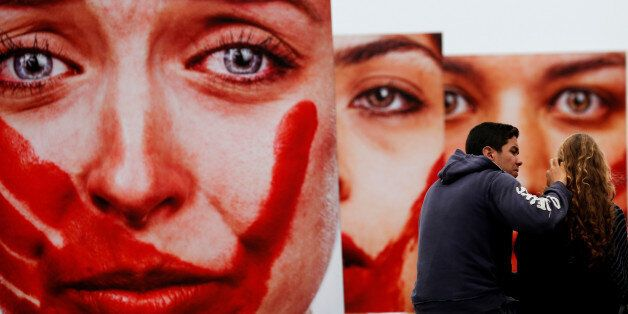 Activists talk in front photos from Brazilian photographer Marcio Freitas, during a protest by non-governmental...
