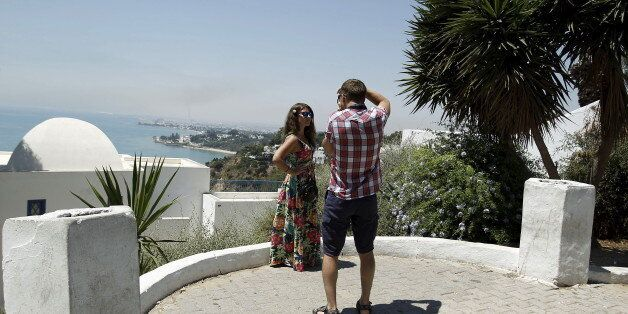 A tourist takes pictures of his partner in Sidi Bou Said, a popular tourist destination near Tunis, Tunisia...