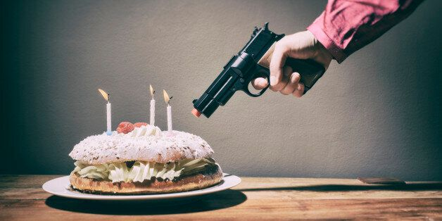 A woman threatens a delicious cream and raspberry birthday or anniversary cake with a toy gun at point...