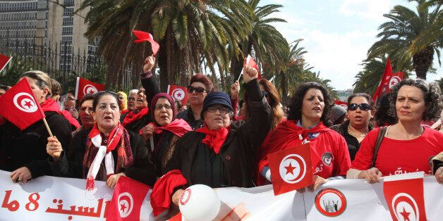 Tunisian women wave flags during a march to celebrate International Women's Day in Tunis March 8, 2014....