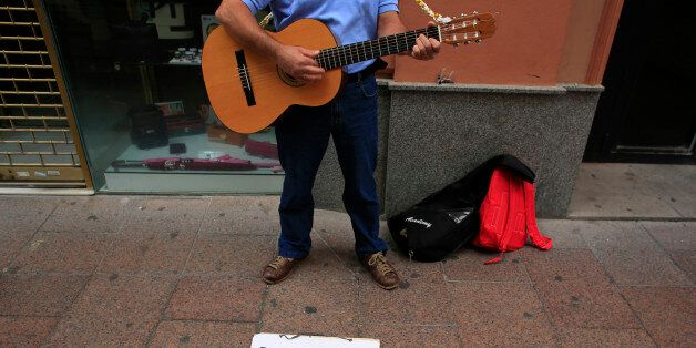 Unemployed Paco, 51, plays his guitar as he ask for alms in the Andalusian capital of Seville, southern...