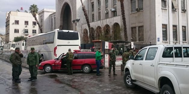 Syrian security forces cordon off the area following a reported suicide bombing at the old palace of...