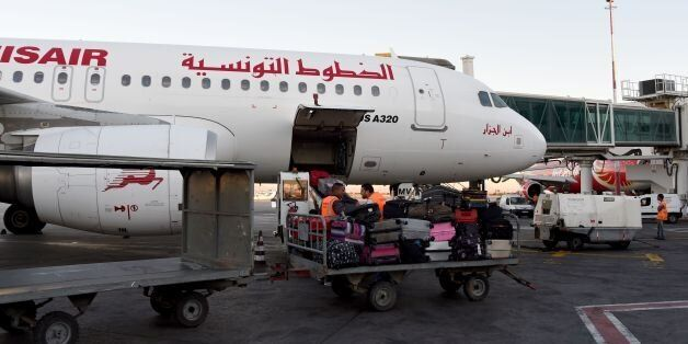 A picture taken on July 19, 2016 at Tunis-Carthage International Airport shows a labourer transporting...