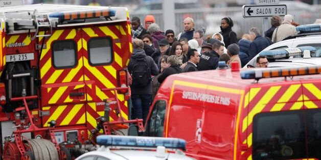 Repeating correcting date - Passengers wait amongst emergency vehicles at Orly airport southern terminal...