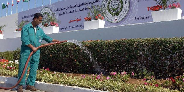TUNIS, TUNISIA: A municipal employee waters 19 May 2004 the flowers in front of the Congress Palace of...