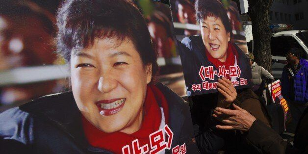 Pro-government activists hold a portraits of South Korean President Park Geun-Hye outside the Constitutional...