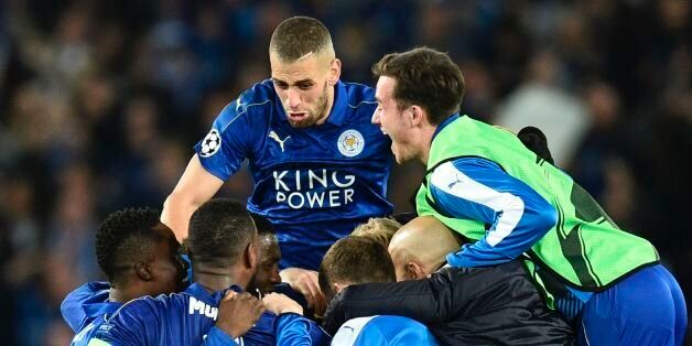 Leicester City's Algerian striker Islam Slimani (CL top) jumps in to celebrate with his Leicester teammates...