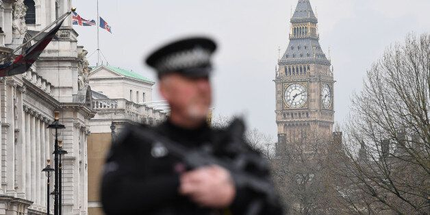 An armed police officer patrols by a security cordon set up along Whitehall by the Houses of Parliament...