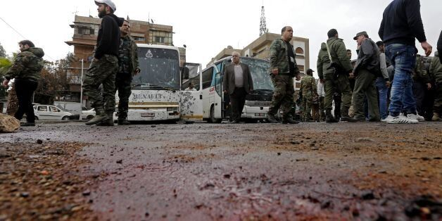Syrian security forces and locals gather at the scene of a bombing following twin attacks targeting Shiite...