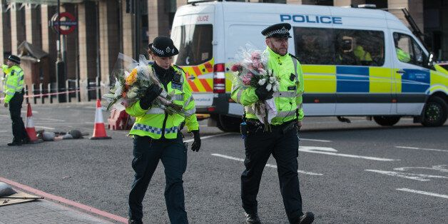 LONDON, ENGLAND - MARCH 23: Police officers arrive with floral tributes on Westminster Bridge following...