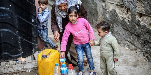 Palestinians filling bottles and jerricans with drinking water at Al-Shati refugee camp in the southern...